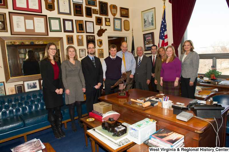 Congressman Rahall stands in his Washington office with nine people.