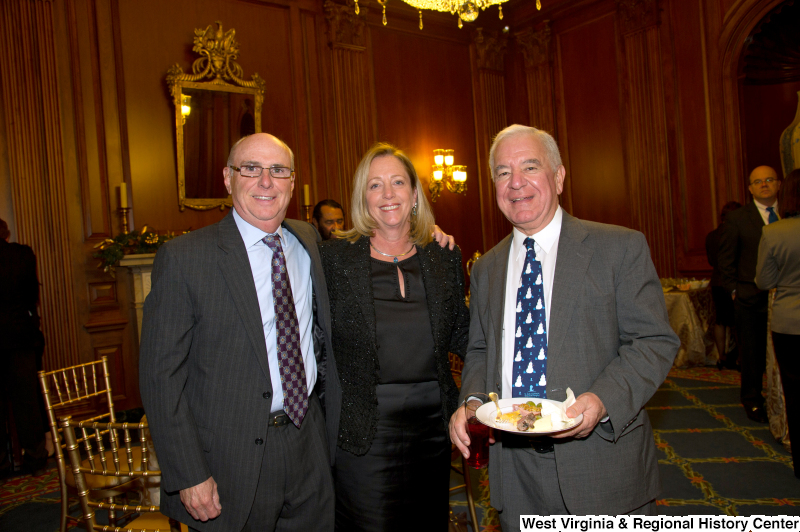 Congressman Rahall stands with a man and a woman at a reception.