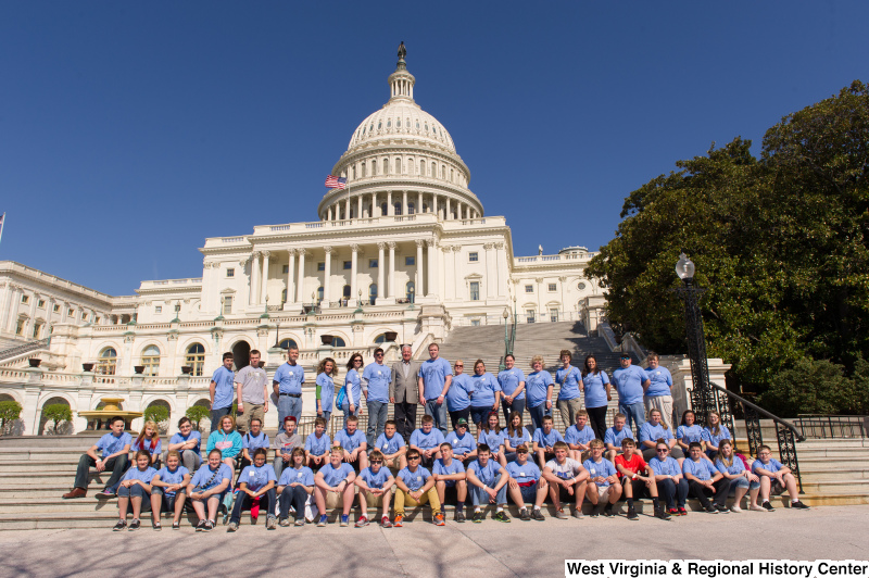 "Congressman Rahall stands on the steps of the Capitol Building with children and adults wearing blue shirts labeled ""MMS 8th Grade D.C. Trip""."