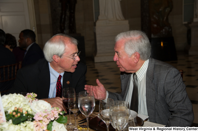 Congressman Rahall speaks to John Barrow at a dinner table.