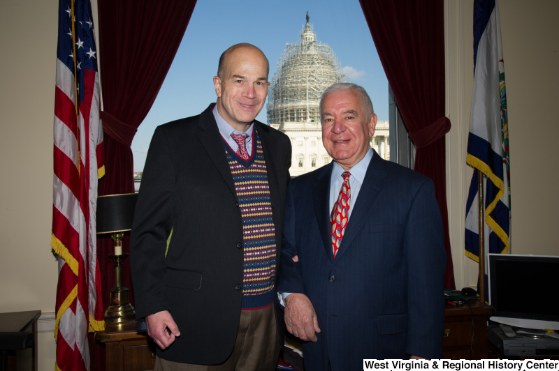 Congressman Rahall stands in his Washington office with a man wearing a dark blazer and multicolored sweater.