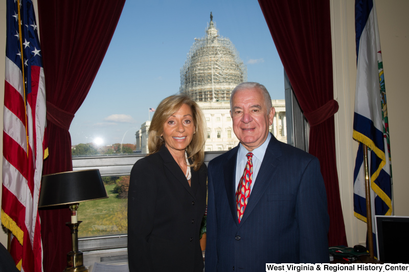Congressman Rahall stands in his Washington office with a woman wearing a dark top and white necklace.