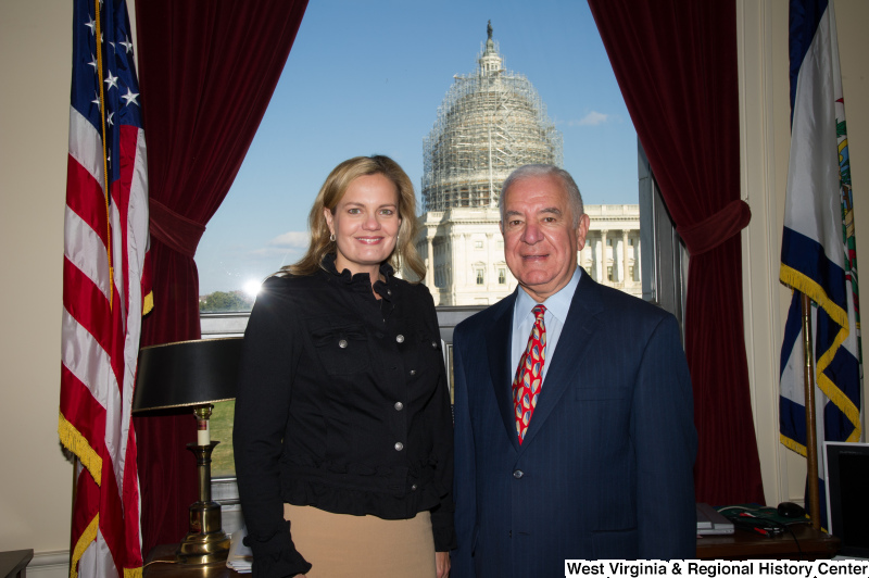 Congressman Rahall stands in his Washington office with a woman wearing a dark top and khaki skirt.