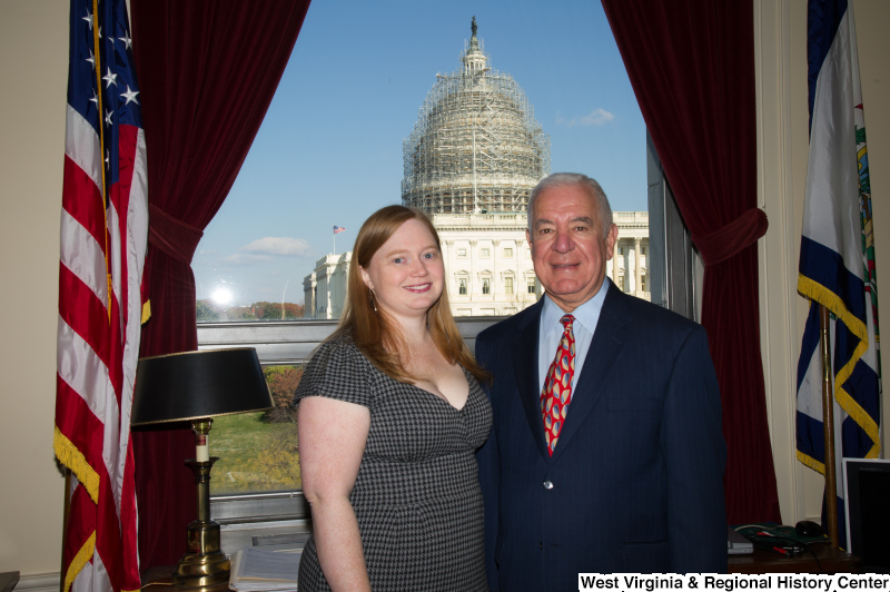 Congressman Rahall stands in his Washington office with a woman wearing a grey and black dress.