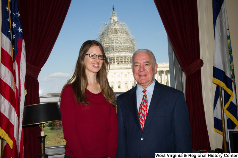Congressman Rahall stands in his Washington office with a woman wearing a red sweater.