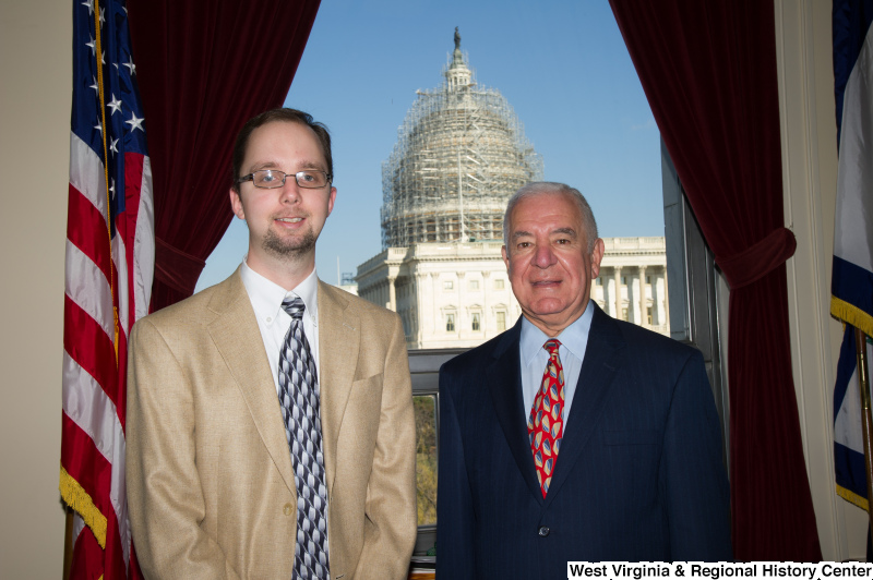 Congressman Rahall stands in his Washington office with a man wearing a khaki sport coat.