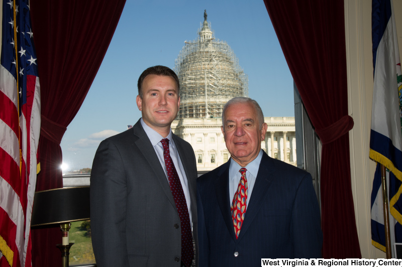 Congressman Rahall stands in his Washington office with a man wearing a grey suit and burgundy spotted tie.