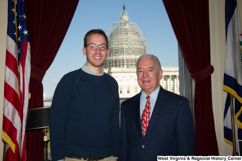 Congressman Rahall stands in his Washington office with a man wearing a blue sweatshirt.