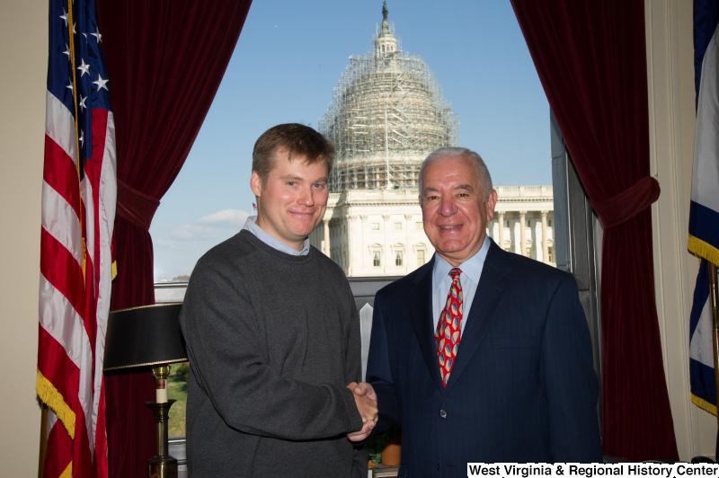 Congressman Rahall stands in his Washington office with a man wearing a grey sweater.